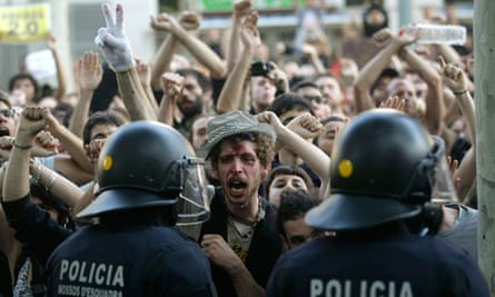 Riot police stand in front of protesters outside the Catalonia regional parliament