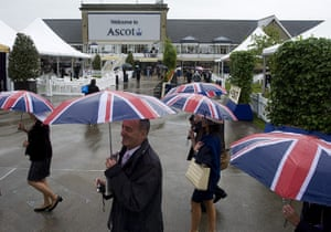 Ascot Ladies Day: Race goers shelter under umbrellas