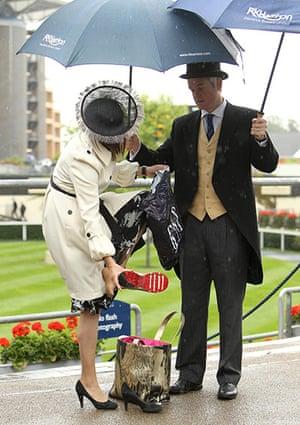 Ascot Ladies Day: A racegoer shelters under an umbrella