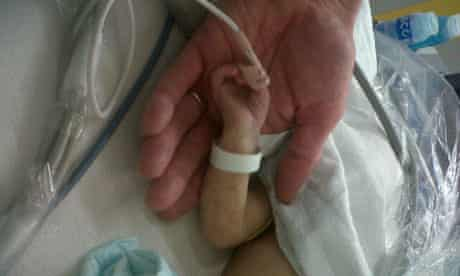 A baby holds a doctor's hand at Great Ormond Street Hospital on 16 June 2011. Photograph: Rowenna Davis for the Guardian