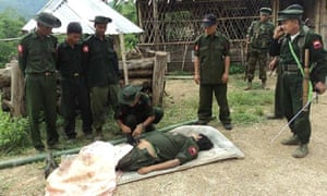 Kachin soldiers gather around the body of a comrade they claim died in fighting with Burmese troops