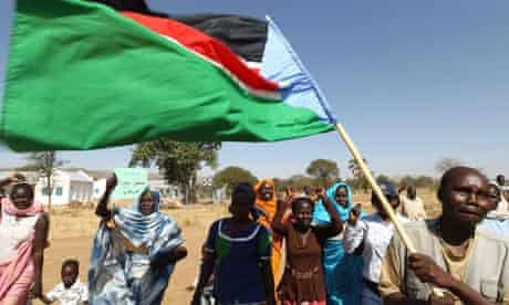 A Sudanese man waves the regional flag