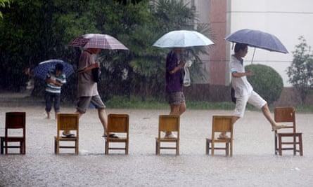 Students cross a flooded school yard in Wuhan