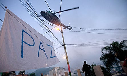 A police helicopter flies over a banner in the Mangueira favela calling for peace