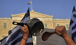 A greek protester beats a saucepan during a rally