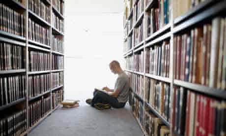 man reading book in library