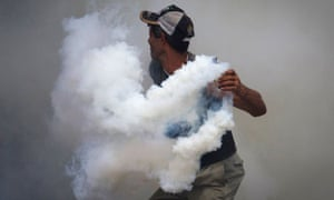 A relative of a prison inmate throws a tear gas canister