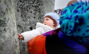 Summer solstice: A baby touches one of the stones as revellers watch the sunrise