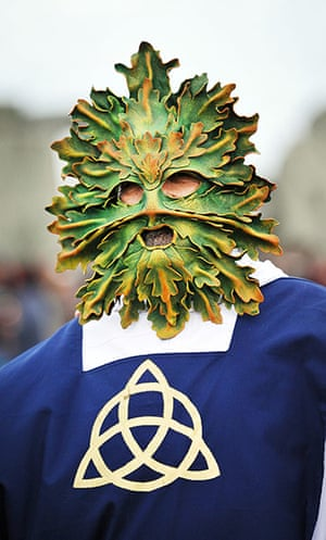 Summer solstice: A druid wears a facemask as revellers watch the sunrise