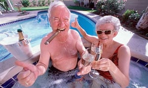 Elderly couple in jacuzzi drinking champagne , man with cigar