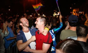 Male friends celebrate as rainbow flags waved in crowd