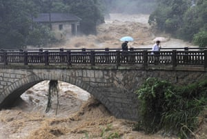 2010 Extreme Weather: Residents walk on a bridge over an overflowing river  Fujian province