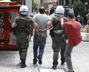 Greece strikes : A demonstrator kicks a policeman