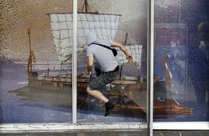 Greece strikes : A protestor attempts to break a window
