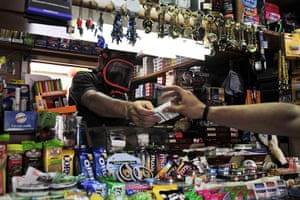 Greece strikes : A kiosk owner wears a gas mask while selling cigarettes