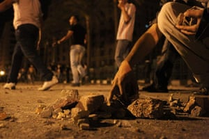 Cairo Clashes: An Egyptian protester collects stones