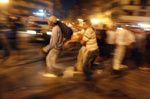 Cairo Clashes: Protesters carry an injured man in Tahrir Square