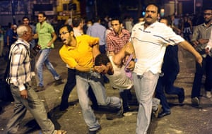 Cairo Clashes: Egyptians carry an injured young man