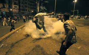 Cairo Clashes: A protester kicks a tear gas canister