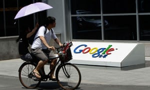A couple cycle past the logo of Google in Beijing