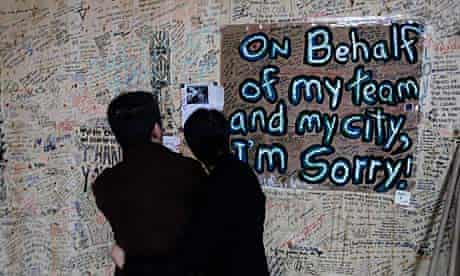Two people look at apologies written on plywood covering a store looted during the Vancouver riots