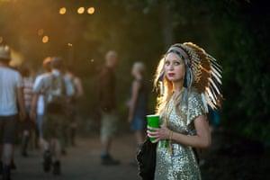 Glastonbury: A woman wearing and Indian head-dress, Glastonbury festival