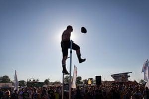 Glastonbury: A performer bound in chains up a ladder, Glastonbury festival