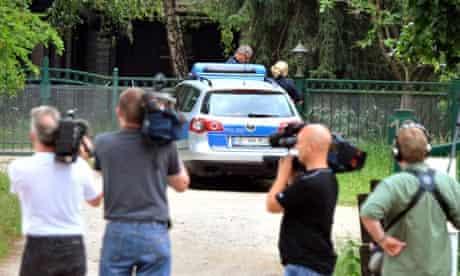 Media gather near a police car outside a farm in Bienenbuettel, in the county of Uelzen, Germany