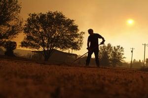 Arizona Wildfires: Wayne Lutz rakes dead grass