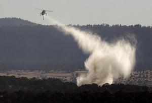 Arizona Wildfires: A sky crane makes a water drop on a spot fire