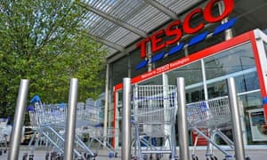 Shopping trolleys are seen in front of a Tesco store in west London