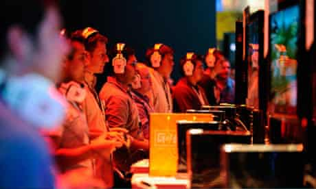 Gamers play video games at the XBOX 360 booth during the E3 expo
