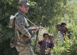 Syrian Refugees: A Turkish soldier stands by as a group of Syrians