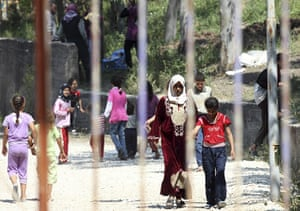 Syrian Refugees: Refugees walk behind the fence of a refugee camp