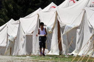 Syrian Refugees: A Syrian refugee walks besides tents