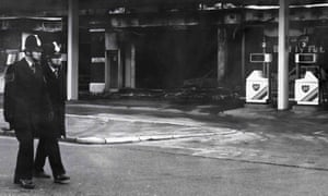 Toxteth Riots: Two policemen walk past a burnt out BP garage