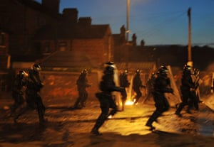 Ardoyne riots: Riot police with battons run towards a crowd of Nationalist youths