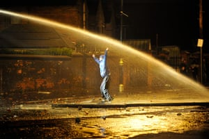 Ardoyne riots: A Nationalist youth dances in defiance as police fire a water cannon