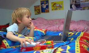 Boy using computer in bedroom