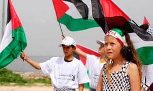 Children display Palestinian flags at a rally near Ramallah