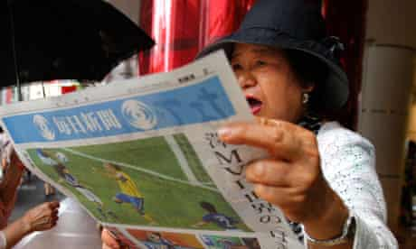 A woman reacts as she reads reports of the women's World Cup victory
