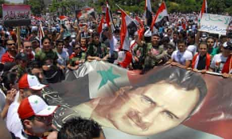 Syrians carry a giant flag bearing a picture of president Bashar al-Assad