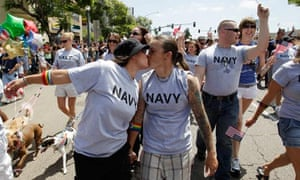 Two women, both active duty sailors in the Navy, kiss during the Gay Pride Parade in San Diego