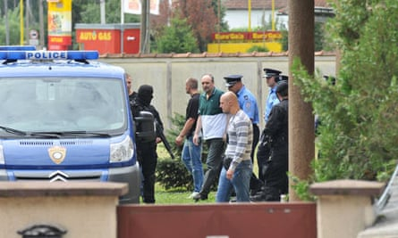 Police secure the area where Goran Hadzic was taken to see his ailing mother before his extradition