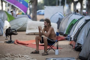 Tent City: An Israeli man plays on a flute amid tents