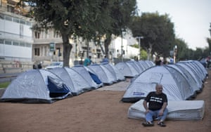 Tent City: A man rests in front of the makeshift homes