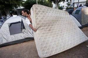 Tent City: A protester carries a mattress to his tent