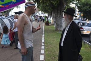 Tent City: An Israeli protester chats to an ultra-Orthodox Jewish man near tents