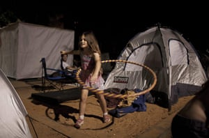Tent City: A girl plays hula hoop outside her tent
