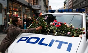 A woman places flowers on a police vehicle after Oslo memorial march